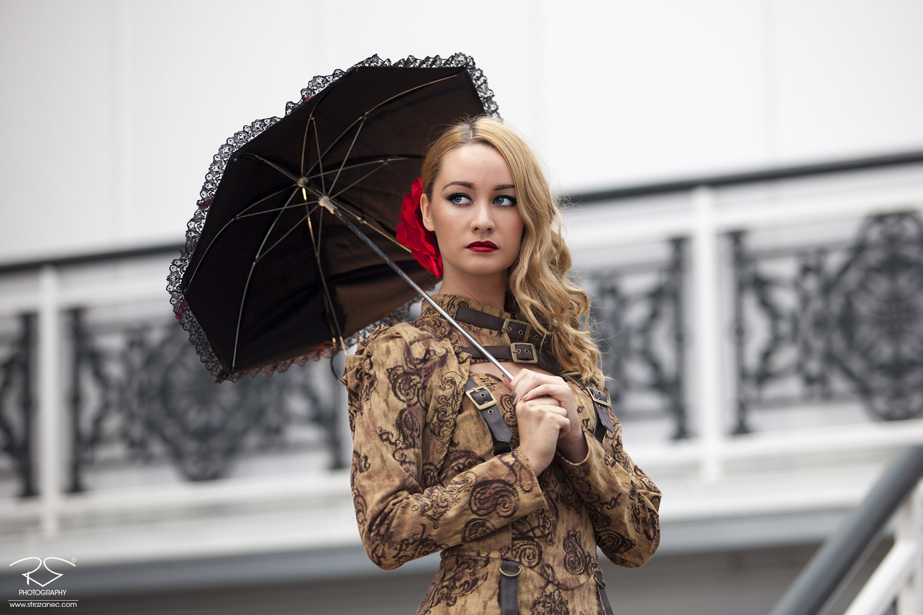 Beautiful blonde girl in steampunk dress with umbrella and red flower in hair.